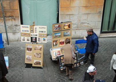 Um vendedor de aguarelas come o seu pão enquanto uma potencial compradora olha para os seus quadros. Será observação ou julgamento?
